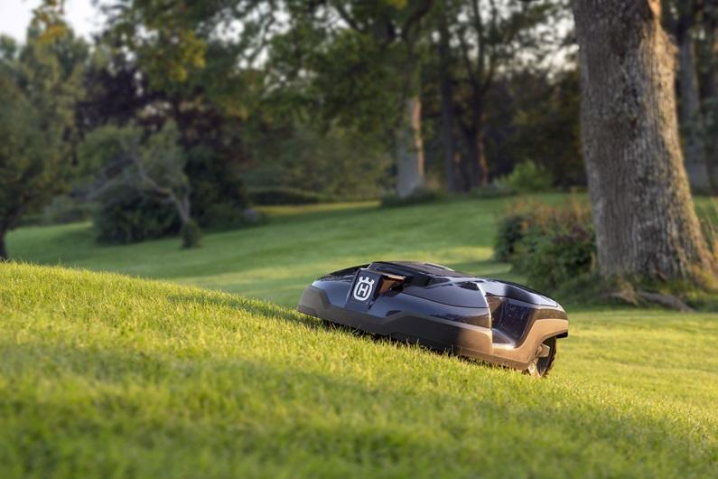 Melns Husqvarna zāles pļāvējs robots – Automower 310 modelis, darbības demonstrācija pļaujot zāli, augšup pa zemes paaugstinājumu