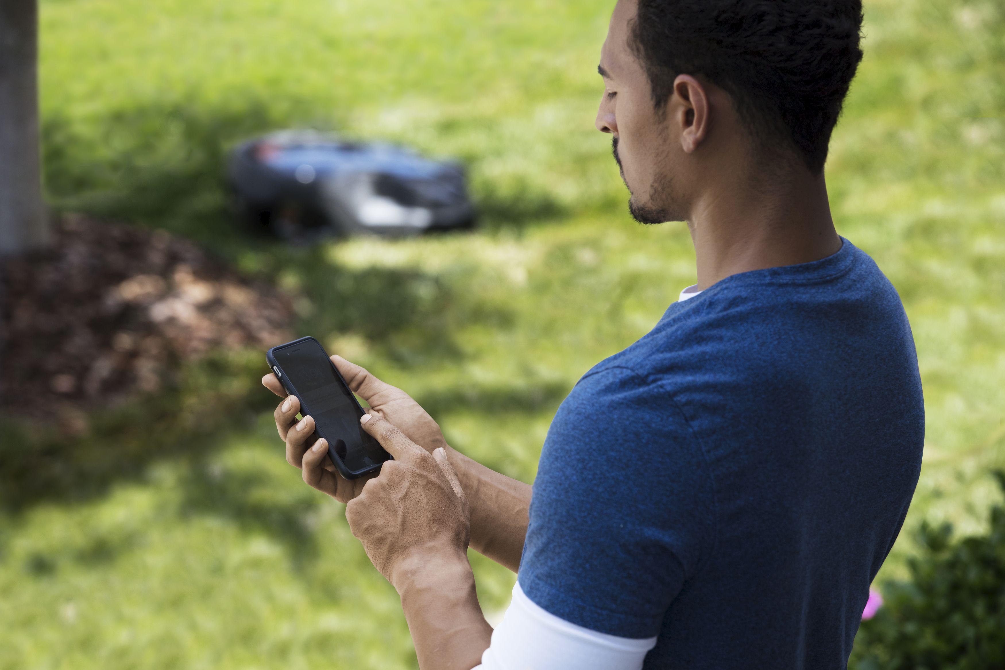 Melns Husqvarna zāles pļāvējs robots – Automower 315Xmodelis, darbības demonstrējums vadībai ar viedtālruni, ko veic vīrietis zilā formā
