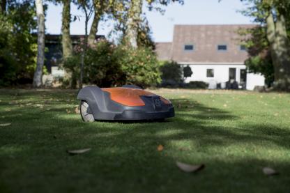 melns ar oranžu zāles pļāvēja robots no sāna skata pļaujot zāli