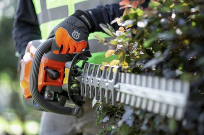 Oranžas Husqvarna Dzīvžogu šķēres, modelis ''522HDR75X'', skats no priekšas, paraugdemonstrācija