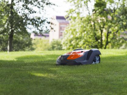 melns ar oranžu zāles pļāvēja robots uz zālāja