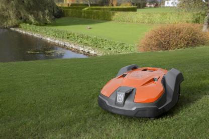 zāles pļāvējs robots uz zālāja pie dīķa
