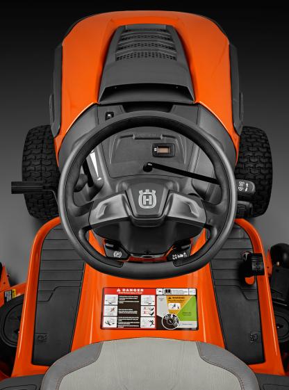 Oranžs Husqvarna zāles pļāvējs traktors, modelis ''TC 138'', skats no vadītāja viets uz vadības paneli