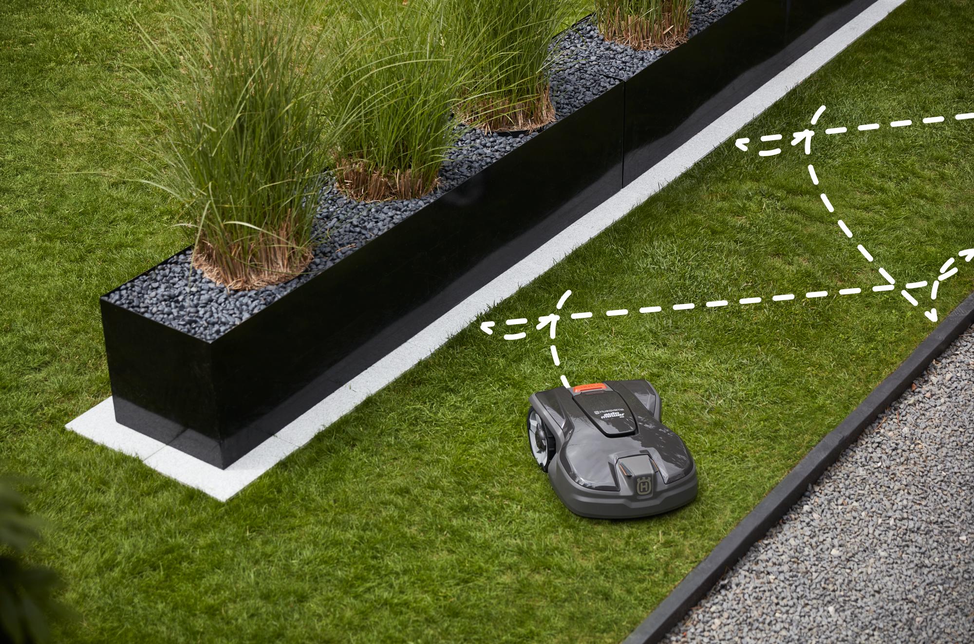melns zāles pļāvējs robots uz zālāja dārzā