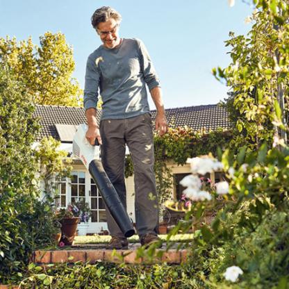 Vīrietis dārzā strāda ar akumulatora lapu pūtēju