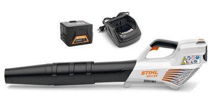 Akumulatora lapu pūtējs no sāna skata ar diviem akumulatoriem un lādētāju