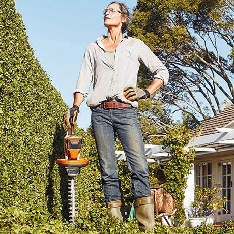 Sieviete stāv ar akumulatora dzīvžoga šķērēm un skatās uz dzīvžogu