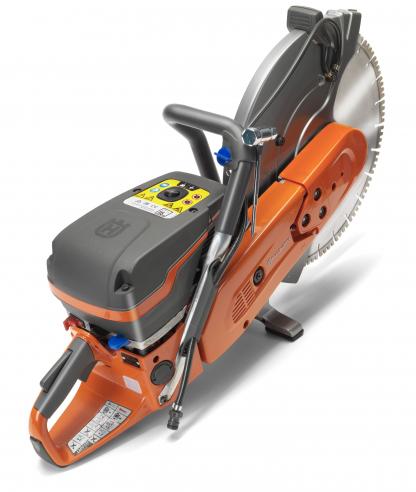 """Oranžs Husqvarna spēka zāģis, modelis """"K970'' ar 16 collu griezējdisku, skats no aizmugures augšas labās puses"""